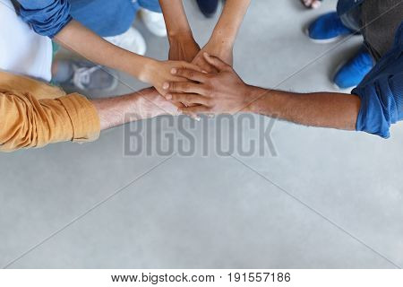 View From Above Of Group Of People Keeping Their Hands In Pile Expressing Social Friendship, Unity,