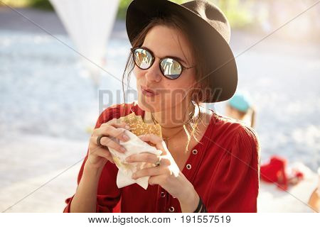 Pleased Woman Wearing Summer Clothes And Trendy Sunglasses Sitting At Terrace Eatting Hamburger Look