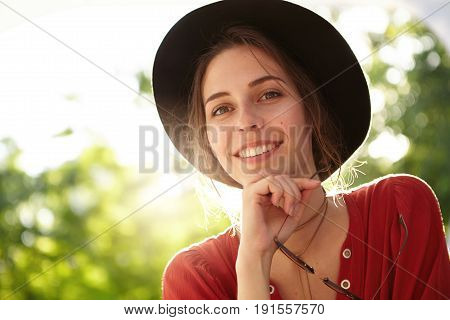 Charming young female with twinkling brown eyes wearing summer hat and red dress holding sunglasses looking pleasantly into camera. Young pretty girl with toothy smile admiring peace resting at nature poster