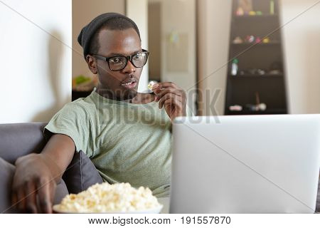 Handsome African Stylish Guy Wearing Elegant Eyeglasses And Black Hat Sitting At Sofa Looking At Lap