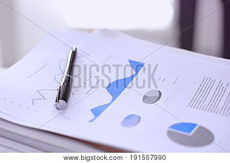 Office workplace with a laptop and financial documents on the light reflecting table