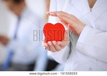 Femail doctor holding a red heart in his hands on a background of the patient. Health care concept
