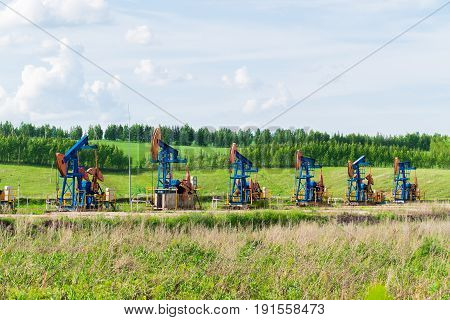 five oil pumps extract oil in the middle of green fields