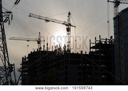 construction site with working crane at dusk