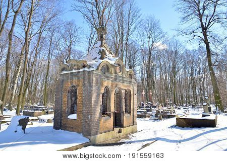 Old stone crypt in Novodevichye Cemetery at sunny winter day close up.