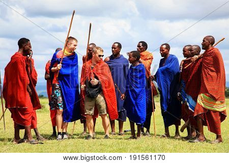 Africa Tanzania - March 04 2016: European tourists interact with the indigenous inhabitants of Africa in the village of the Masai tribe.