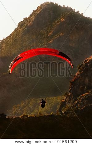The flight of paragliders in the highlands. Paragliding at dawn. Taking photos from a height.