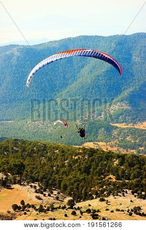 Turkey Oludeniz - June 23 2015: The flight of paragliders in the highlands. Paragliding. Taking photos from a height.