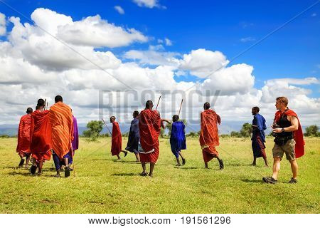 Africa Tanzania - March 04 2016: European tourists interact with the locals of Africa in the village of the Masai tribe.