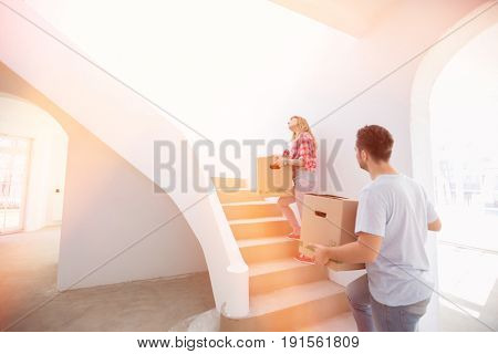 Couple carrying moving boxes up stairs in new house