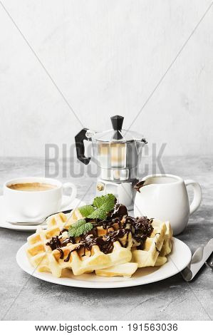Waffles On White Plate With Chocolate And Mint, Coffee, Sauce-boat With Chocolate On A Light Backgro