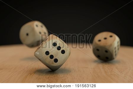 Rolling down three dice on a wooden desk with a black background