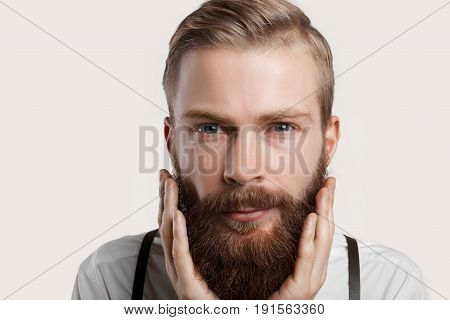 Handsome man touch his beard. Close up portrait of stylish bearded hipster on neutral background. Attractive young person expertising his face before shaving.