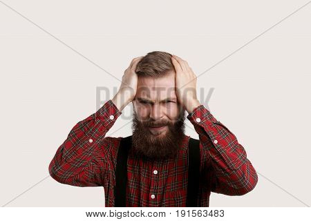Man feel terrible headache. Sick guy want to go to doctor. Guy dismissed from the job in crisis time. European person keep head by two hands and wait for a help.