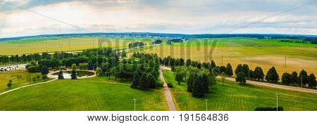 Panoramic rural area. Green fields meadows trees pond roads and sky with clouds. Minsk region Belarus