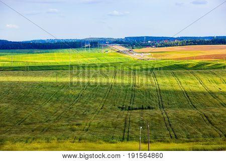 Meadows and fields. Green rural area under blue sky. Summer landscape. Minsk region Belarus.