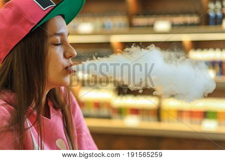 Vape Woman. Portrait Of Young Cute Girl In Pink Hoodie And A Cap Smoking An Electronic Cigarette In