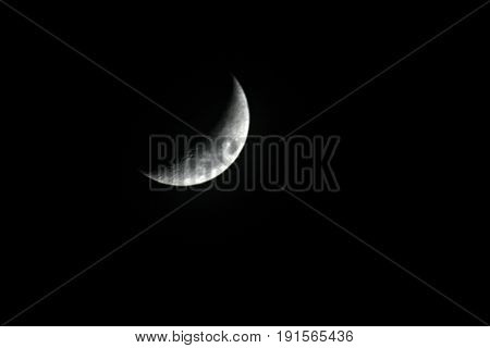 Crescent moon in dark sky A crescent moon showing in the skies with dark background