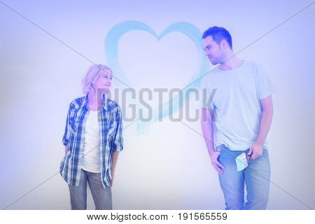 Mid-adult couple looking at each other with painted heart on wall