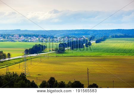Bright summer countryside landscape. Meadows fields trees road and houses in the countryside. Minsk region Belarus