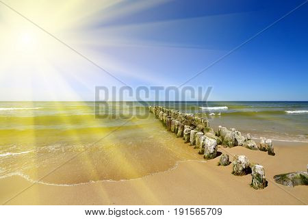 Breakwater on the beautiful sandy beach of the Baltic sea in sunny day