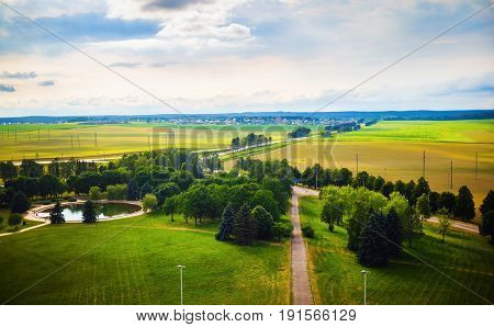 Green countryside landscape. Fields meadows trees pond roads houses on the horizon and sky with clouds. Minsk region Belarus
