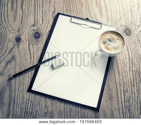 Photo of clipboard with blank letterhead pencil eraser and coffee cup on wooden background. Responsive design template with plenty of copy space.