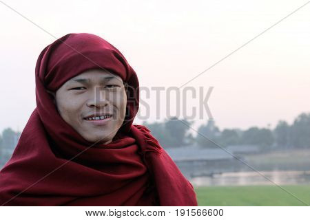 U-BEIN BRIDGE/AMARAPURA, MYANMAR JAN 22: Portrait of a buddhist monk crossing the U-Bein bridge January 22, 2016, U-Bein bridge/Amarapura.