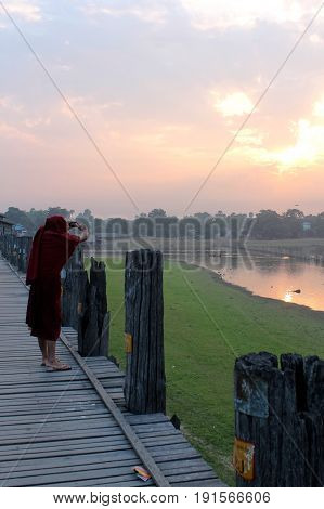 U-BEIN BRIDGE/AMARAPURA, MYANMAR JAN 22: Buddhist monk capturing the sunrise Taungthaman lake with his mobile phone January 22, 2016, U-Bein bridge/Amarapura.