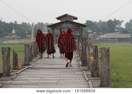 U-BEIN BRIDGE/AMARAPURA, MYANMAR JAN 22: Buddhist monks on their daily walk across the bridge in the early morning hours January 22, 2016, U-Bein bridge/Amarapura.