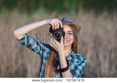 Attractive Young Blonde Woman In Blue Plaid Shirt Straw Hat Enjoying Her Time Taking Photos On Meado