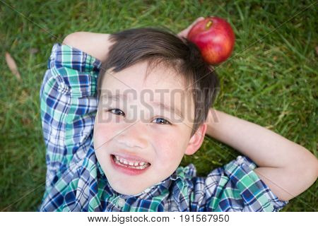 Mixed Race Chinese and Caucasian Young Boy With Apple Relaxing On His Back Outside On The Grass.