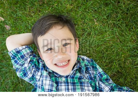 Mixed Race Chinese and Caucasian Young Boy Relaxing On His Back Outside On The Grass.