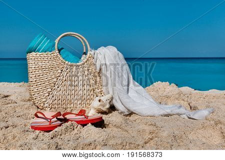 Straw beach bag on exotic sand beach with blue ocean and sky as a background in Cancun Mexico