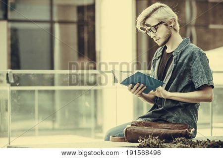 Male fashion student concept. Guy holding and studying from notebook wearing jeans outfit and eccentric sunglasses sitting on white ledge next to modern building