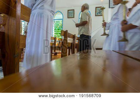 Alofi, Niue - May 29, 2017; Low point of view indoors of Pacific Island man inside church holding hum sheet signs while procession enters Saint Joseph's Catholic Church Alofi Niue
