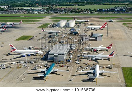 LONDON UK - JUNE 3 2017: Commercial airliners parked near the northern fuel supplies at London's busy Heathrow Airport on a sunny summer morning. Planes using the facility include British Airways Americal Airlines Cathay Pacific and Qantas.