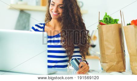 Smiling woman online shopping using computer and credit card in kitchen .