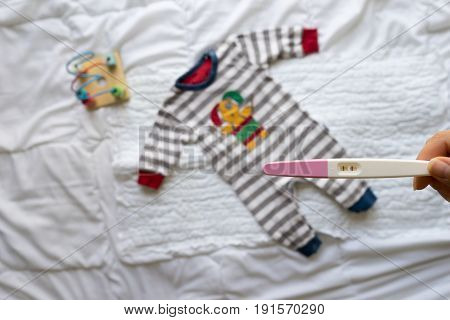 Positive Pregnancy Test In Woman Hand And Baby Clothes On White Background