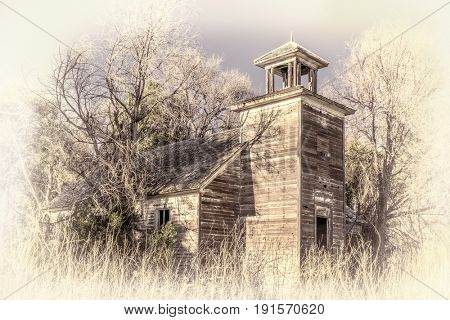 old abandoned schoolhouse in rural Nebraska overgrown by trees and weeds, retro hand tinted opalotype processing