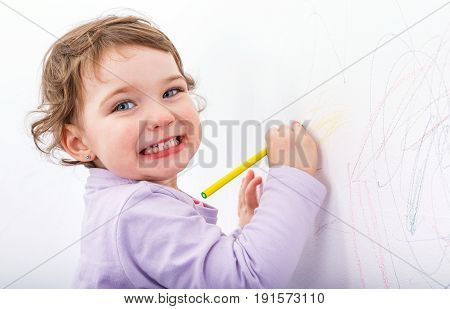 Photo of adorable child drawing on the wall