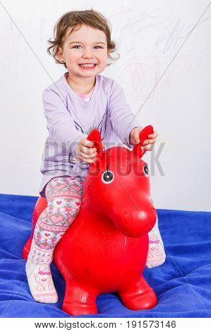 Adorable sweet child playing with a toy horse