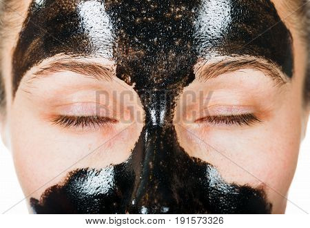 Young woman with facial black mask on isolated white background