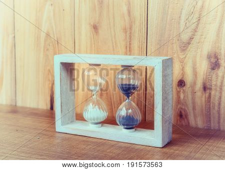 Hourglass on wooden background