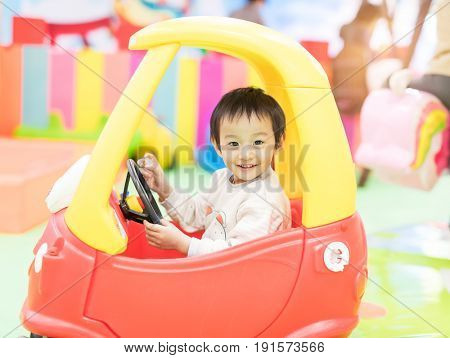 Asian Chinese little girl playing with toy car house at playground.