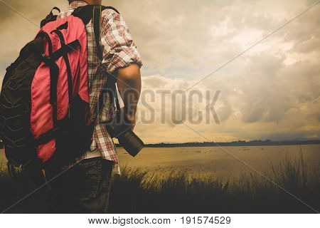 Traveler Man with red backpack and digital camera landscape on background Lifestyle travel success concept summer vacations outdoor