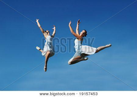 Ballerinas jumping against a blue sky