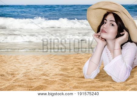 photography with scene of the portrait of the young beautiful girl on beach in straw hat