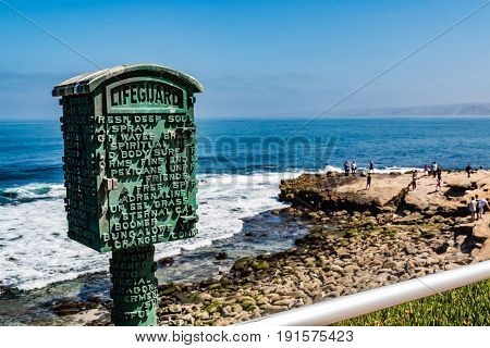 LA JOLLA, CALIFORNIA - JUNE 16, 2017:  Block letter poetry on a lifeguard emergency call box and memorial to lifeguard David C. Freeman, who drowned at Boomer Beach.