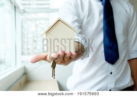 Hand agent with home in palm and key on finger. Offer of purchase house rental of Real Estate. Giving offering demonstration handing house keys.